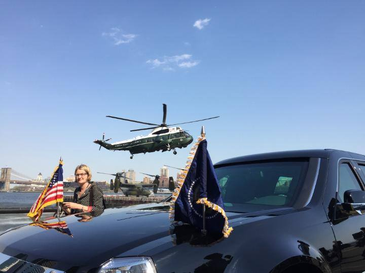 Angela Greiling Keane next to presidential limo with Marine One preparing to land in the background.